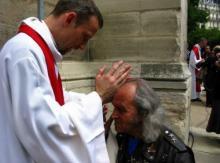 Le père Guy Gilbert reçoit la bénédiction d'un prêtre qui vient d'être ordonné